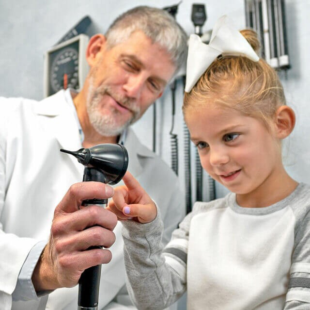 physician and pediatric patient interacting with Wispr Digital Otoscope in exam room